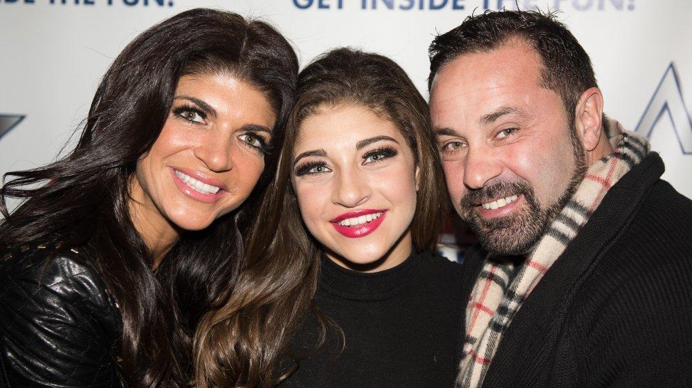 Teresa Giudice, Gia Giudice et Joe Giudice souriant et embrassant lors d'un événement sur le tapis rouge