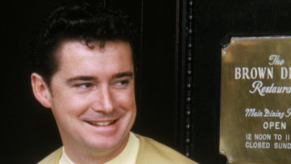 Un jeune Regis Philbin souriant et regardant à sa gauche