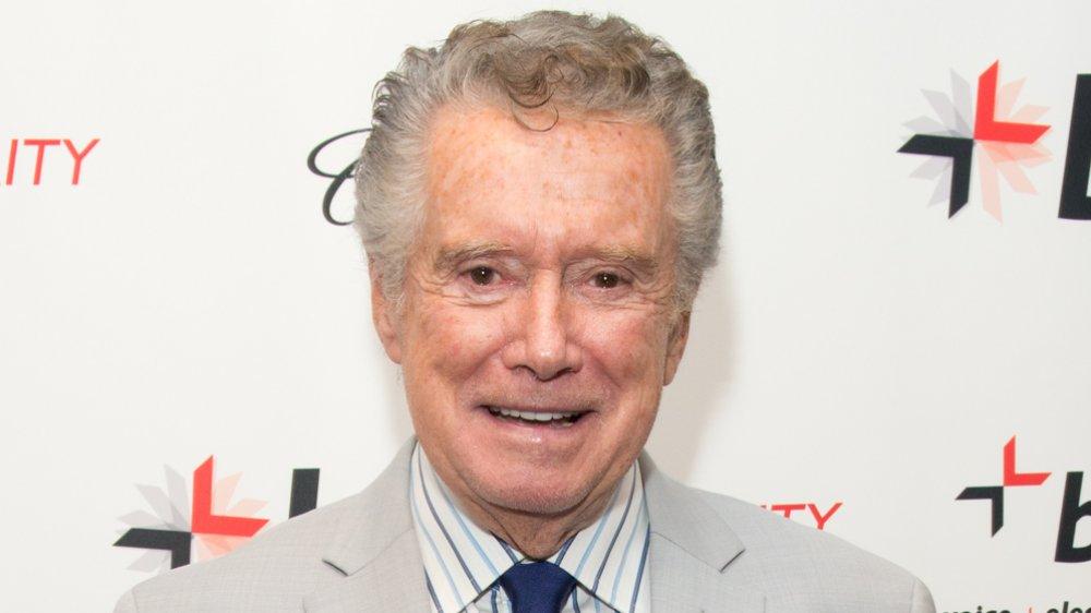 Regis Philbin dans un costume beige et une cravate bleue, avec un petit sourire lors d'un événement sur le tapis rouge
