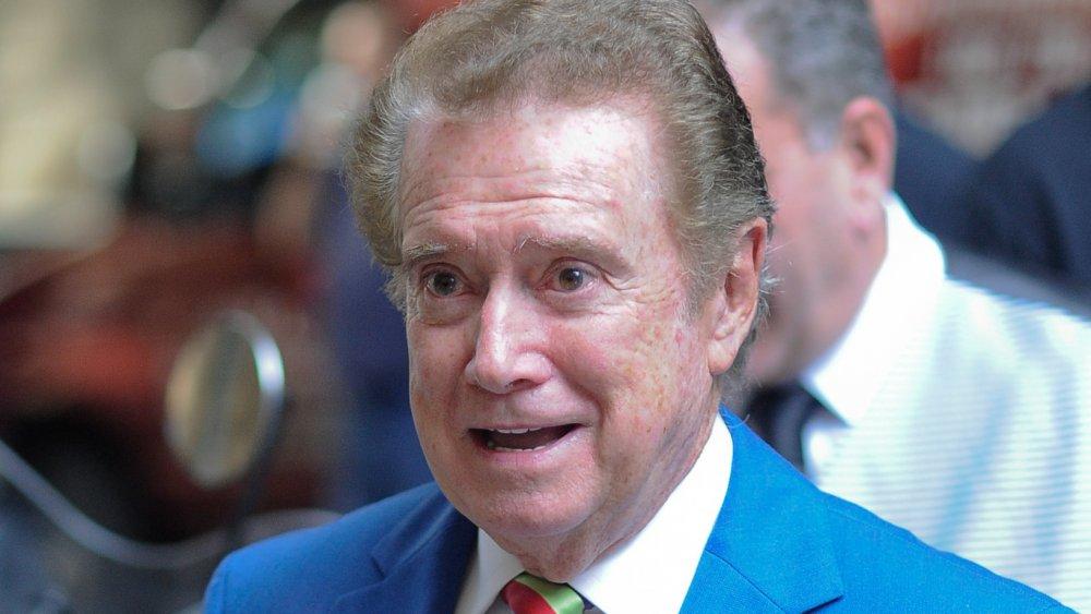 Regis Philbin dans un costume bleu clair et une cravate rayée multicolore, parlant