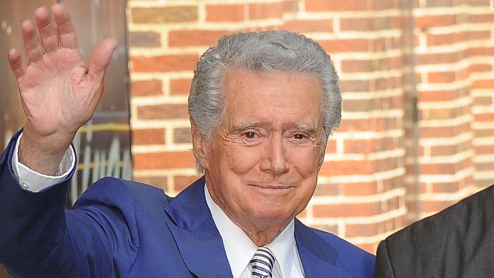 Regis Philbin dans un costume bleu, agitant, avec un petit sourire