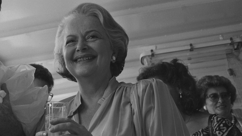 Photo en noir et blanc d'Olivia de Havilland souriant et tenant un verre