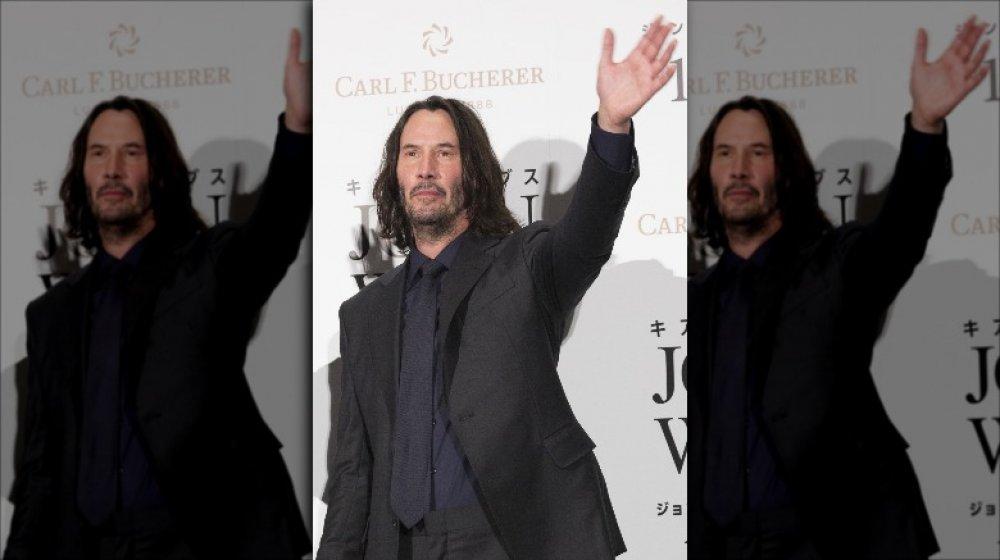 Keanu Reeves dans un costume gris foncé, aux cheveux plus longs, agitant lors d'un événement sur le tapis rouge