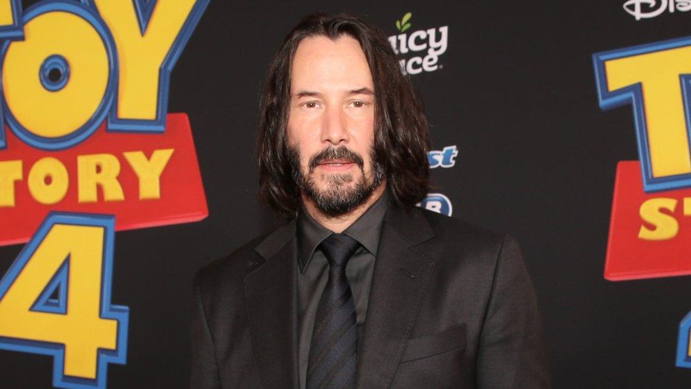 Keanu Reeves portant un costume noir avec une cravate rayée bleu et noir, assistant à la première de Toy Story 4