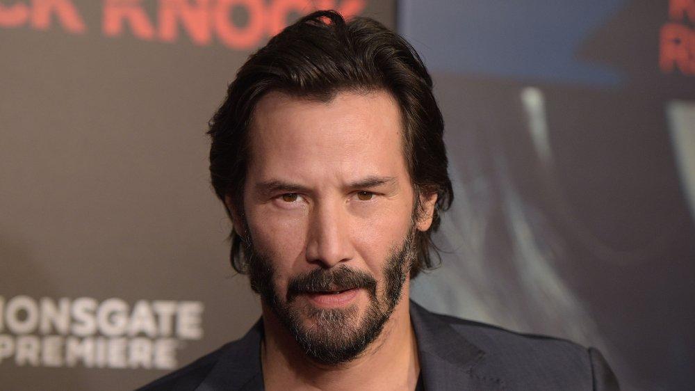 Keanu Reeves dans un blazer gris foncé et une chemise noire, aux cheveux plus courts, lors d'une première