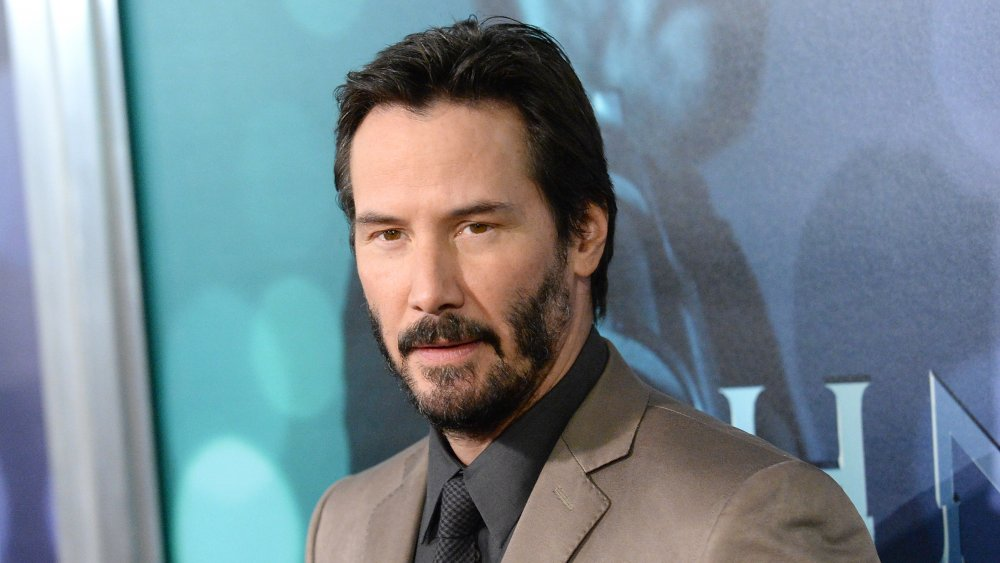 Keanu Reeves portant un costume beige et une chemise noire, aux cheveux courts, lors d'une première de film
