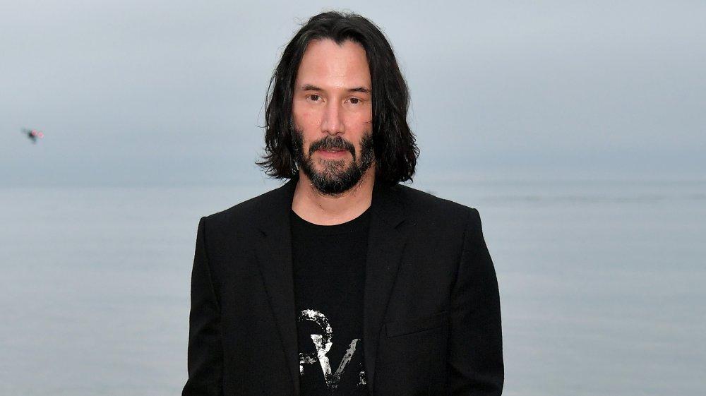 Keanu Reeves dans un long blazer noir et un t-shirt noir, avec des cheveux mi-longs, posant sur la plage