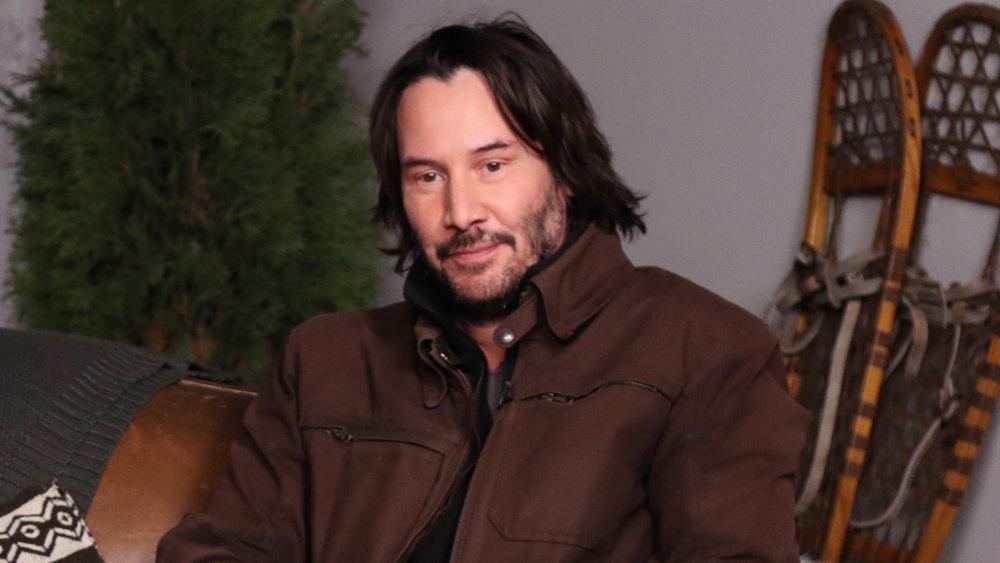 Keanu Reeves dans une veste marron, assis et posant avec un petit sourire à Sundance