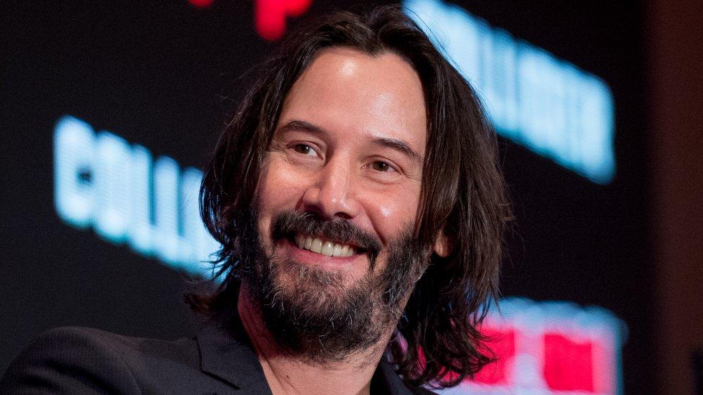 Keanu Reeves portant un blazer noir et une chemise à col en v, souriant lors d'un panel Comic Con