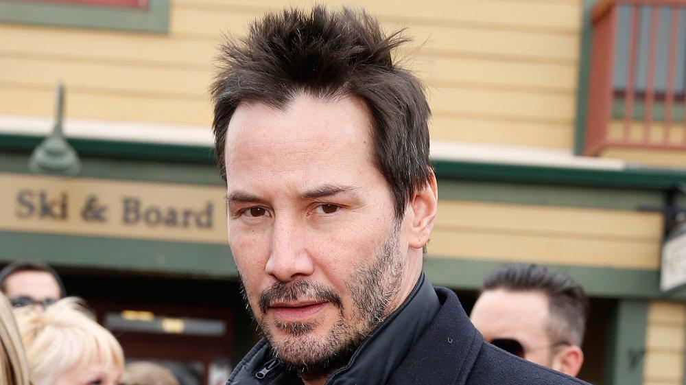 Keanu Reeves portant un caban noir, avec des cheveux plus courts et hérissés, regardant droit vers la caméra avec une expression sérieuse