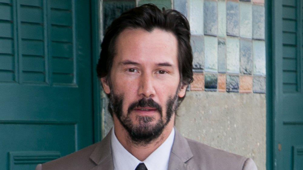 Keanu Reeves dans un costume beige et une chemise blanche, aux cheveux plus courts, regardant directement la caméra avec une expression neutre