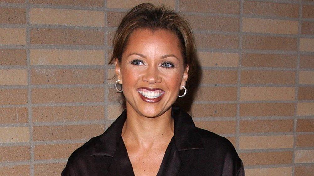Vanessa Williams souriant devant un mur de briques