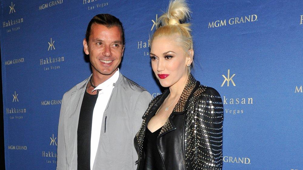Gavin Rossdale souriant et portant une veste grise, et Gwen Stefani en veste en cuir noir avec une expression neutre, posant ensemble