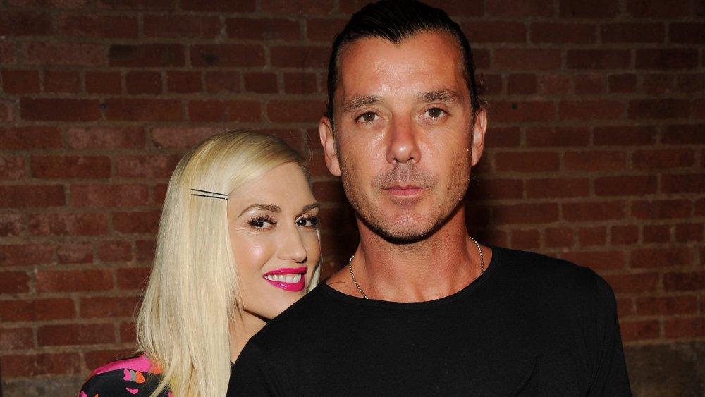 Gwen Stefani dans une robe rose et noire, souriant par derrière Gavin Rossdale
