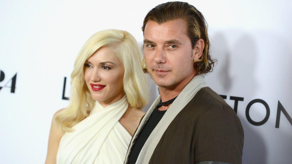 Gwen Stefani souriant dans une robe blanche courte et Gavin Rossdale avec une expression sérieuse dans un blazer marron