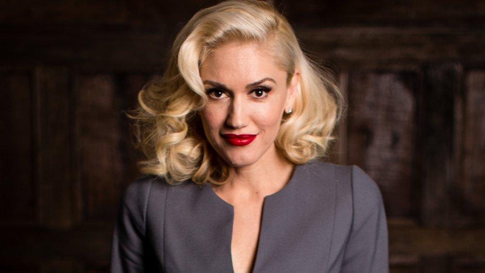 Gwen Stefani dans une tenue grise et rouge à lèvres, posant avec un petit sourire