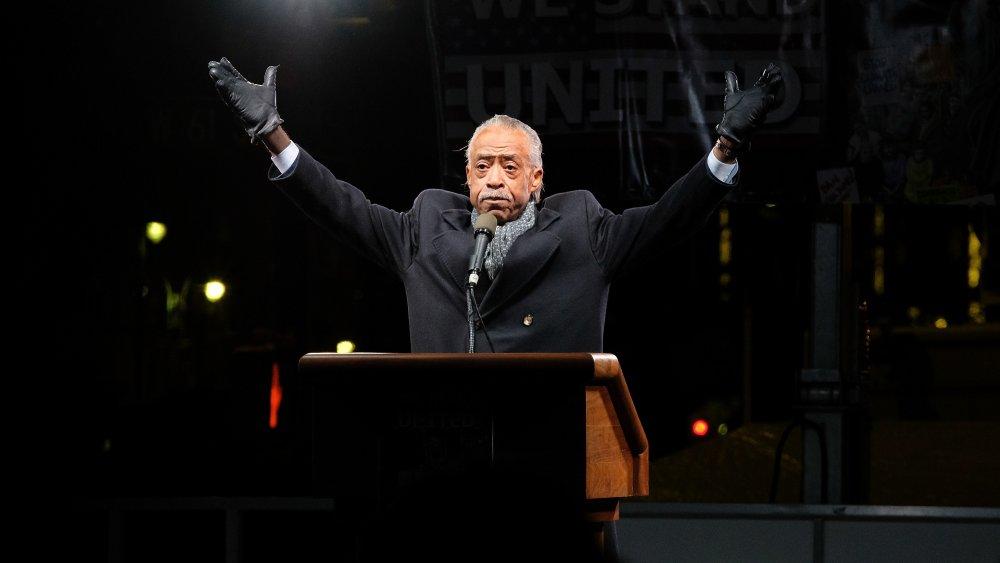 Al Sharpton portant des gants noirs avec les deux bras levés