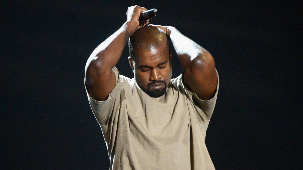 Kanye West dans un t-shirt beige, tenant sa tête avec les yeux fermés sur scène