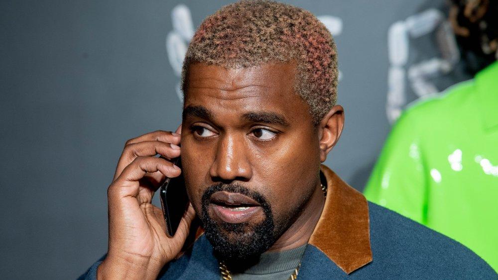 Kanye West dans un blazer bleu et marron, parlant au téléphone