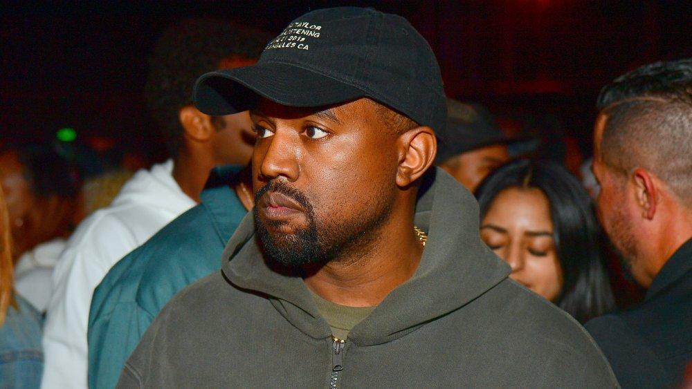 Kanye West dans un sweat à capuche gris et un chapeau noir, avec une expression sérieuse lors d'un événement