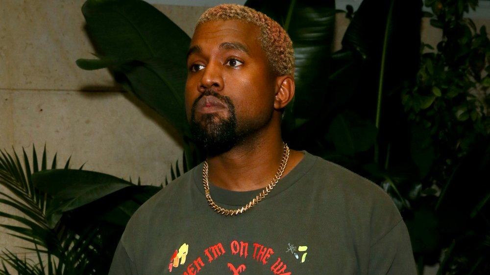Kanye West dans un t-shirt gris imprimé et une chaîne en or, regardant sur le côté avec une expression sérieuse