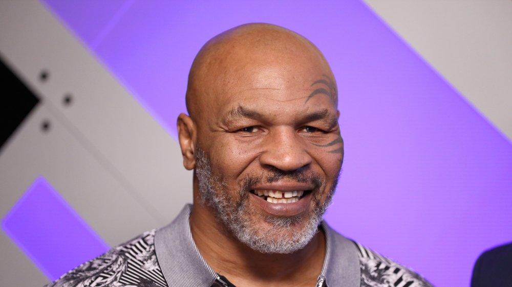 Mike Tyson souriant devant un mur violet