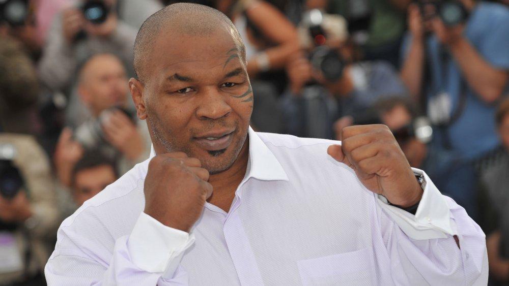 Mike Tyson avec les poings levés, posant en chemise blanche