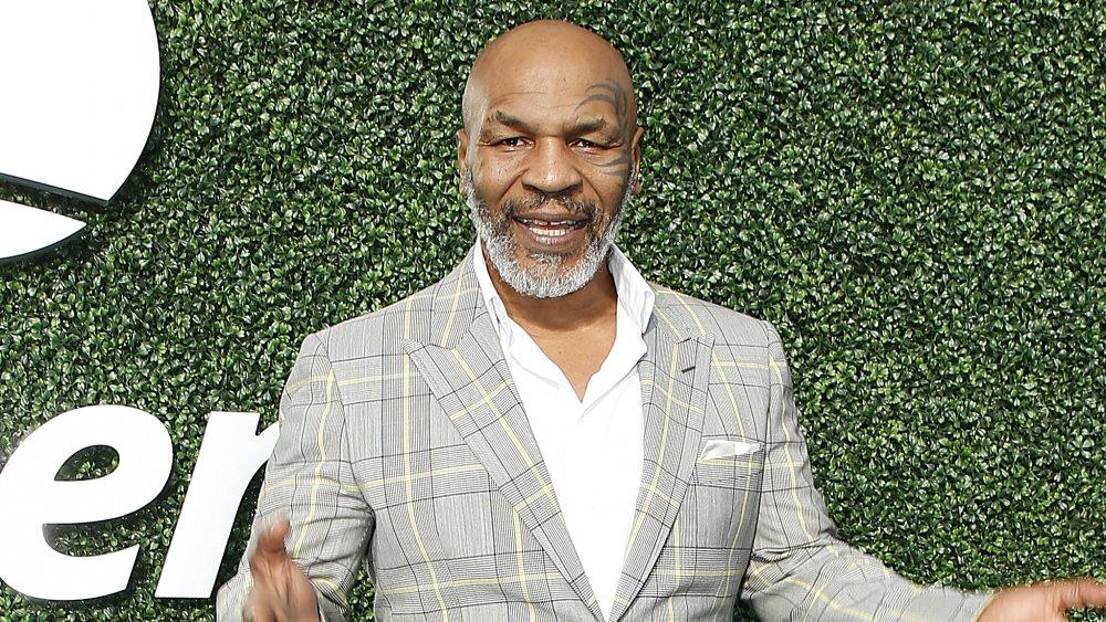 Mike Tyson posant devant un mur herbeux dans un blazer à carreaux