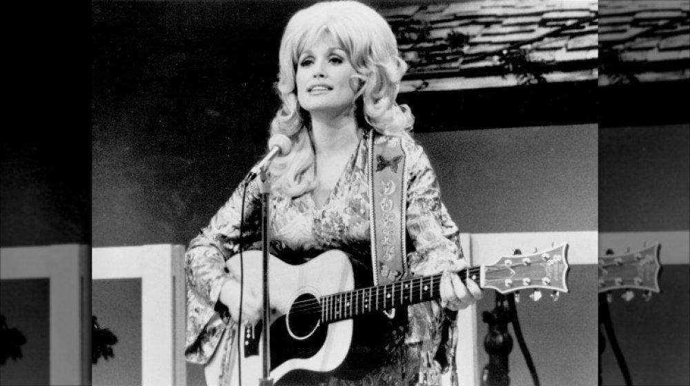 Photo en noir et blanc de Dolly Parton chantant et jouant de la guitare en 1974 à 28 ans