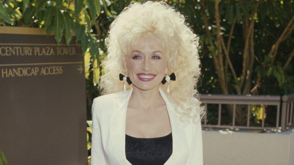 Dolly Parton sourit grand dans un costume blanc et un haut noir en 1985 à 39 ans