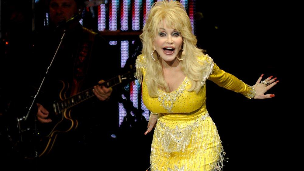 Dolly Parton en robe jaune scintillante, sur scène en 2011 à 65 ans