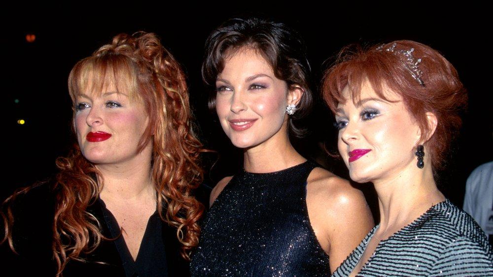 Wynonna Judd, Ashley Judd, Naomi Judd debout avec de petits sourires lors d'une première de film