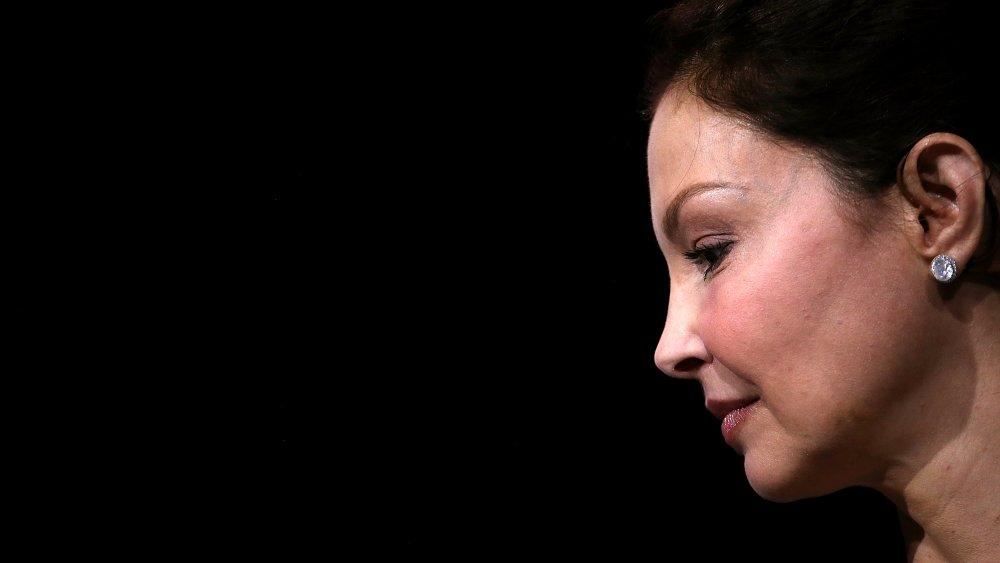 Profil d'Ashley Judd sur fond noir, regardant vers le bas avec une expression neutre