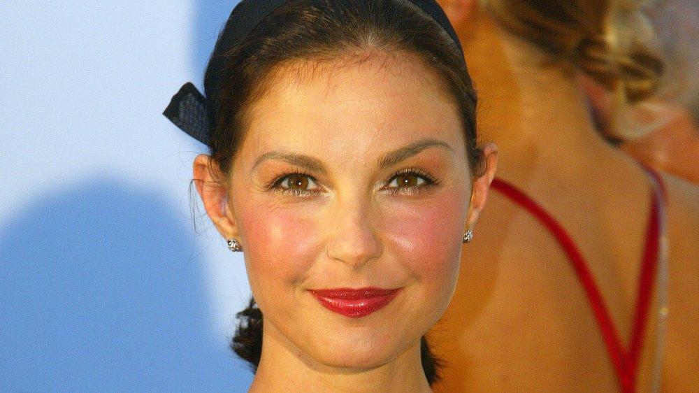 Ashley Judd avec ses cheveux tirés en arrière, souriant un doux sourire tout en regardant directement la caméra