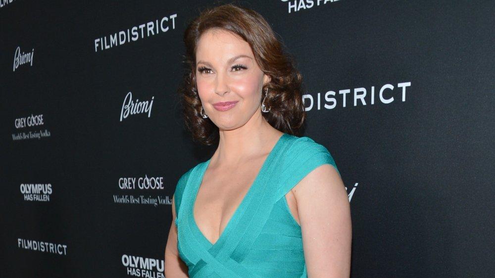 Ashley Judd dans une robe bleu sarcelle, souriant et posant avec une main sur sa hanche sur le tapis rouge