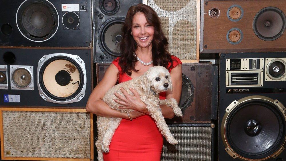 Ashley Judd dans une robe rouge et un collier de perles blanches, souriant tout en tenant son chien décédé, Shug