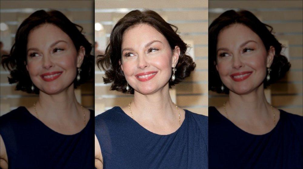 Ashley Judd dans une robe bleue, souriant grand tout en regardant sur le côté
