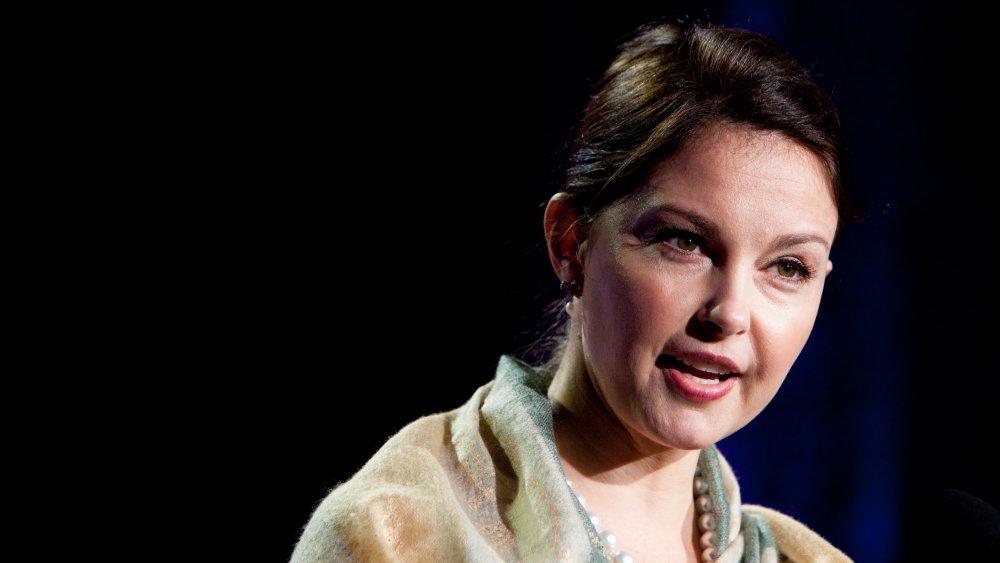 Ashley Judd dans un collier de perles claires et multicolores et de perles blanches, s'exprimant lors d'un événement