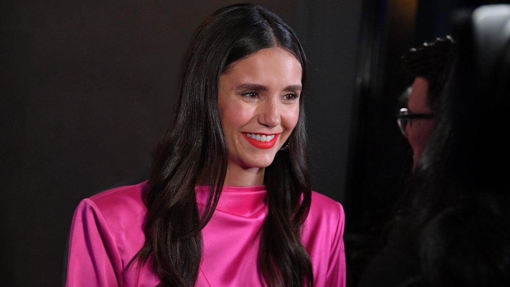 Nina Dobrev dans une robe rose vif, souriant lors d'une conversation