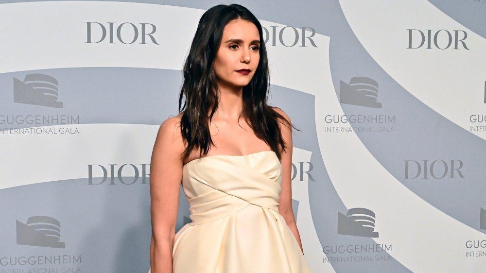 Nina Dobrev dans une robe crème sans bretelles, posant sous un angle avec une expression sérieuse