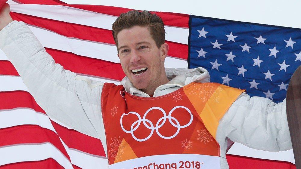 Shaun White souriant et tenant le drapeau américain aux Jeux Olympiques d'hiver de 2018