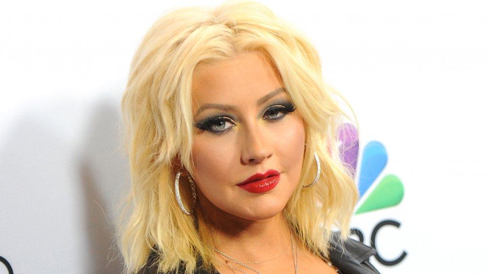 Christina Aguilera dans une veste en cuir noir et boucles d'oreilles cerceau d'argent, regardant l'appareil-photo avec une expression sérieuse