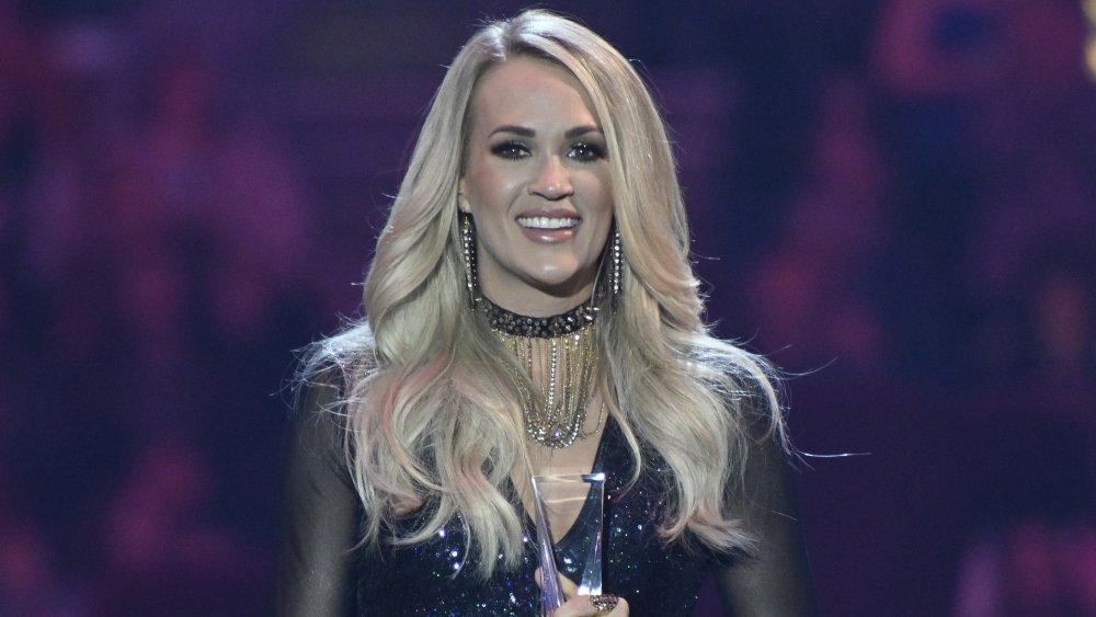 Carrie Underwood dans une tenue scintillante noire, souriant tout en acceptant un prix