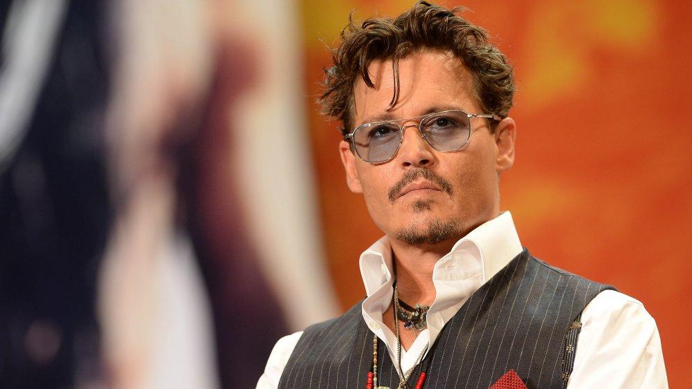 Johnny Depp en chemise blanche, gilet gris et lunettes de soleil teintées de gris