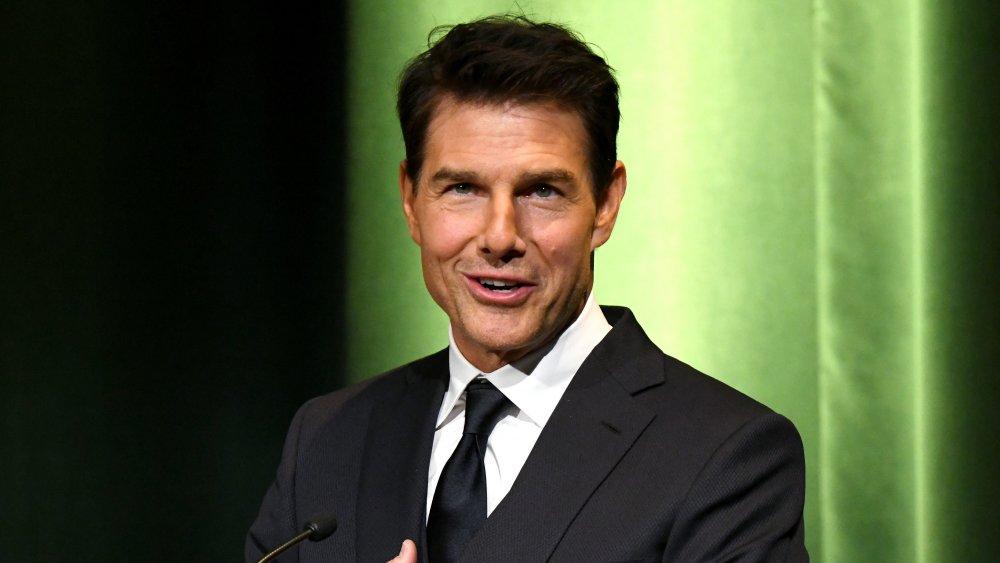 Tom Cruise s'exprimant sur un podium, devant le mur vert