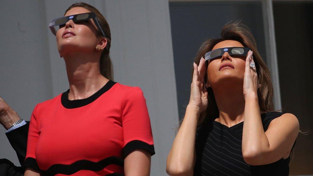 Ivanka Trump dans une robe rouge et noire, Melania Trump dans une robe noire à rayures, à la fois levant les pieds et portant des lunettes pour regarder une éclipse