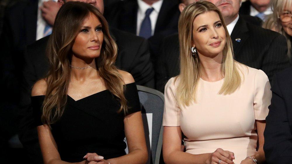 Melania Trump, dans une robe noire, assise à côté d'Ivanka Trump, dans une robe rose clair, à la fois avec des sourires doux