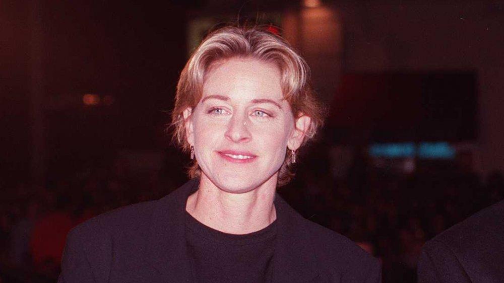 Ellen DeGeneres en costume noir, posant avec un petit sourire au début des années 90