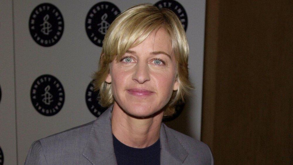 Ellen DeGeneres dans un costume gris et un t-shirt bleu, posant avec un petit sourire