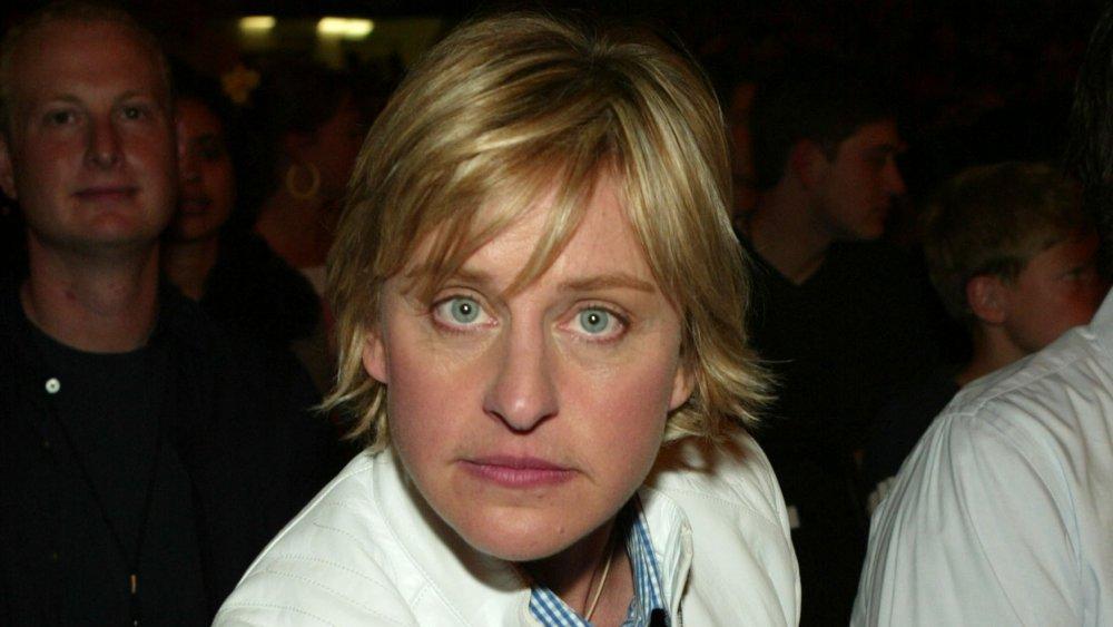 Ellen DeGeneres dans une chemise à carreaux bleu et veste blanche, regardant directement dans la caméra avec une expression neutre